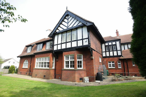 color photo of large red brick faux Tudor house.