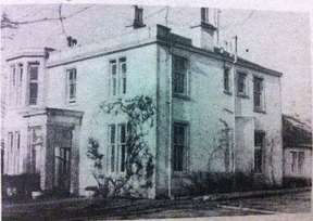 discolored black and white photo of two story house.